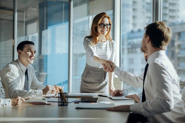 Mejor cooperación. encantadora joven llevando a cabo una reunión con los socios comerciales de su empresa y un apretón de manos con uno nuevo