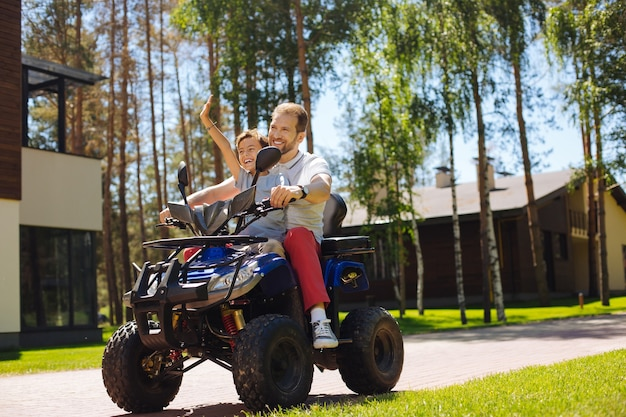 Mejor día. padre joven feliz sonriendo y conduciendo un vehículo todo terreno con su hijo