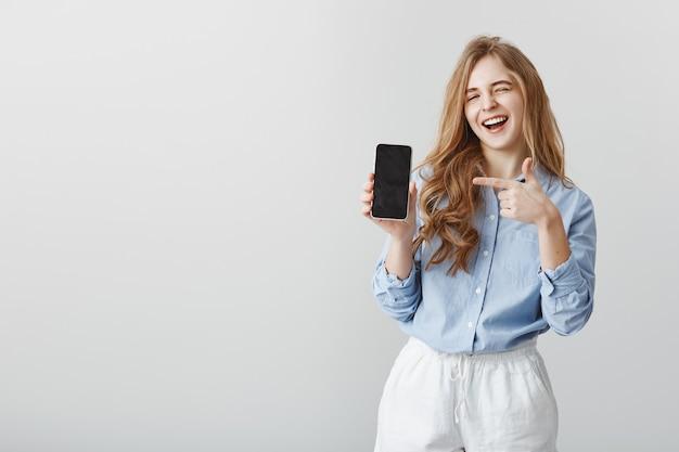 La mejor elección de todas. retrato de guapo modelo de mujer caucásica con cabello rubio en blusa azul, guiñando un ojo y sonriendo mientras muestra el teléfono inteligente y apunta al dispositivo con el dedo índice, promocionando