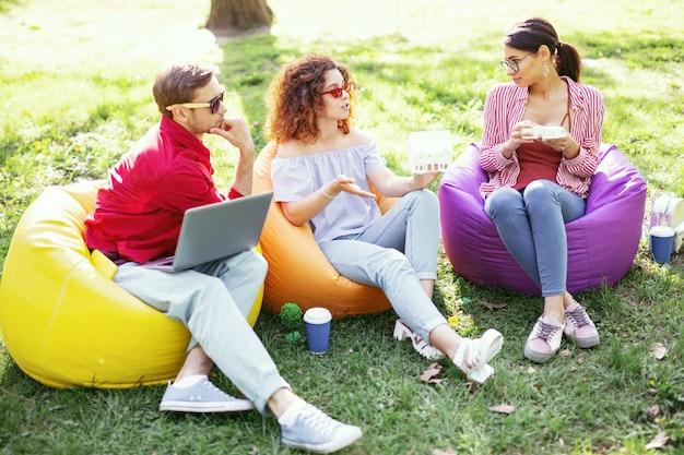 El mejor equipo. compañeros decididos y ambiciosos sentados al aire libre y trabajando en el proyecto