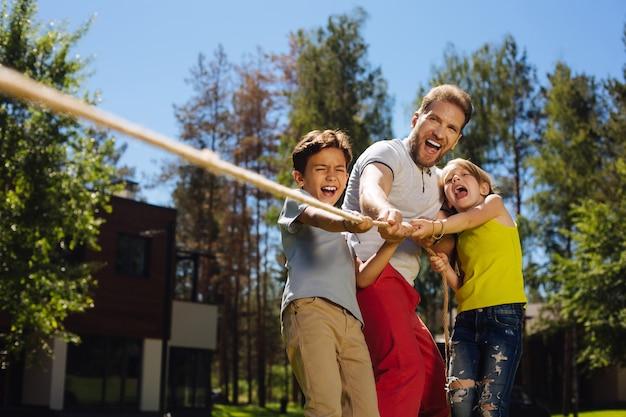 El mejor equipo. papá fuerte inspirado sonriendo y tirando de una cuerda con sus hijos