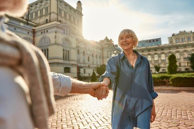 La mejor esposa jamás hermosa pareja senior tomados de la mano y sonriendo mientras baila al aire libre en un