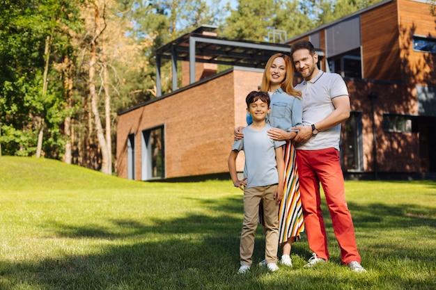 Mejor familia. padres amorosos felices sonriendo y de pie con su hijo