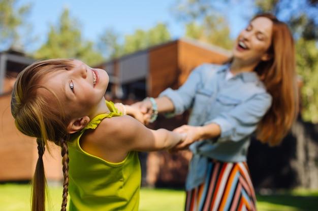 La mejor mamá de todas. madre rubia alegre sonriendo y divirtiéndose con su hija