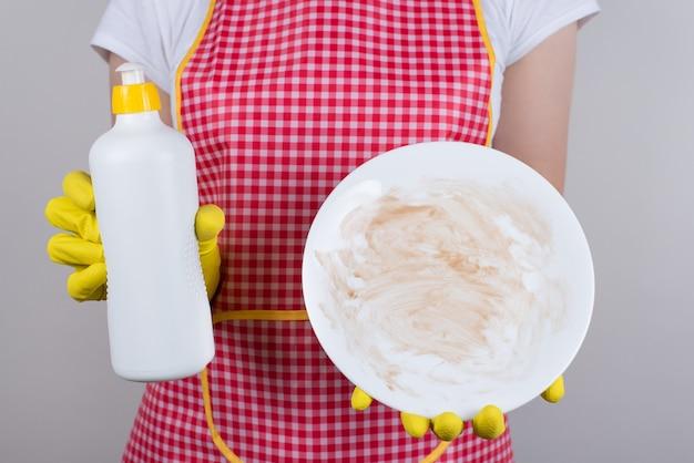 El mejor producto para eliminar la grasa de la vajilla es utilizar un buen concepto de detergente. recortada cerca del trabajador del restaurante molesto que muestra el espacio en blanco de la placa de salsa de chocolate aislada pared gris