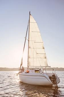 Mejor relajarse vista del barco de vela o yate flotando en el mar con relajado hombre senior sentado en el