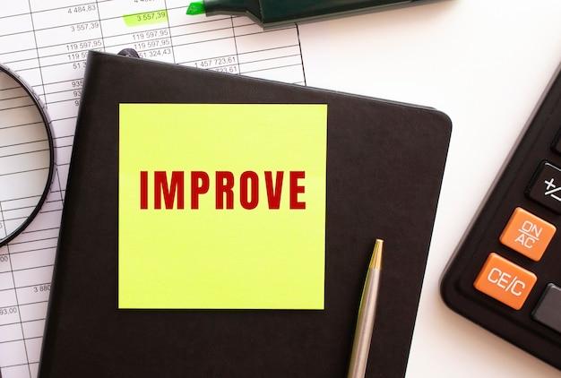 Mejora el texto de una pegatina en tu escritorio. diario, calculadora y bolígrafo. concepto financiero.