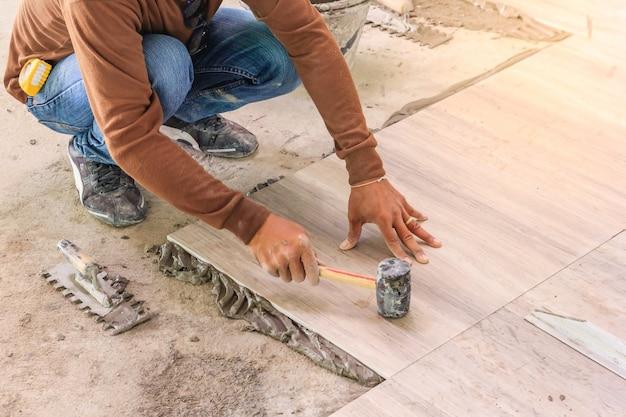 Mejoras para el hogar, renovación - trabajador de la construcción de baldosas es baldosas