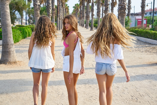 Las mejores amigas adolescentes caminando en palmeras.