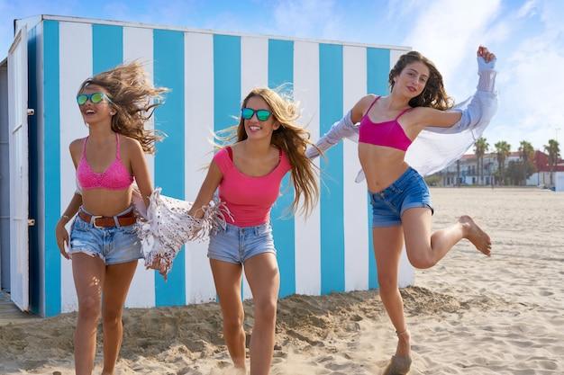 Mejores amigas adolescentes corriendo felices en la playa