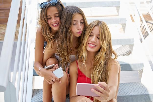 Las mejores amigas adolescentes en fila con un teléfono inteligente.
