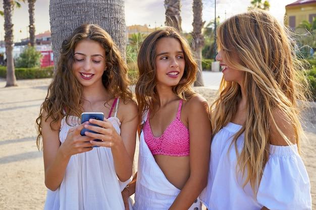 Las mejores amigas adolescentes juegan con un teléfono inteligente.