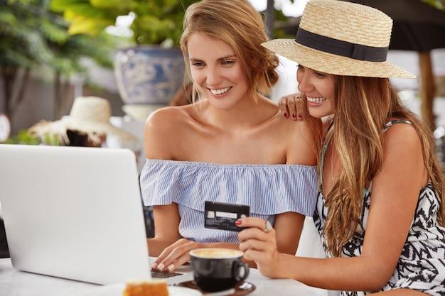 Las mejores amigas jóvenes relajadas usan una tarjeta de crédito y una computadora portátil portátil para realizar el pago, pagan la compra en la tienda web, se sientan en el acogedor interior de la cafetería, toman café, tienen sonrisas agradables