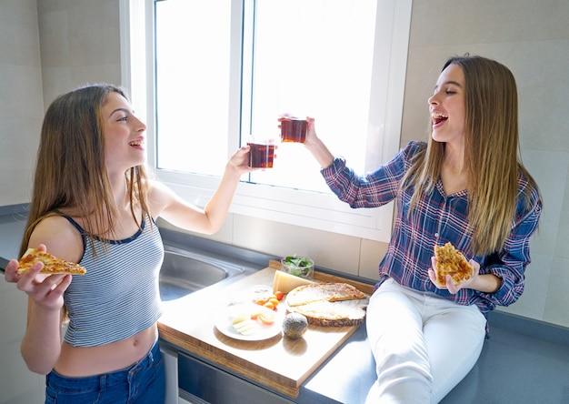 Las mejores amigas que comen pizza en la cocina.