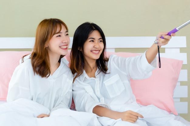 Mejores amigos adolescentes alegres con selfie en cama