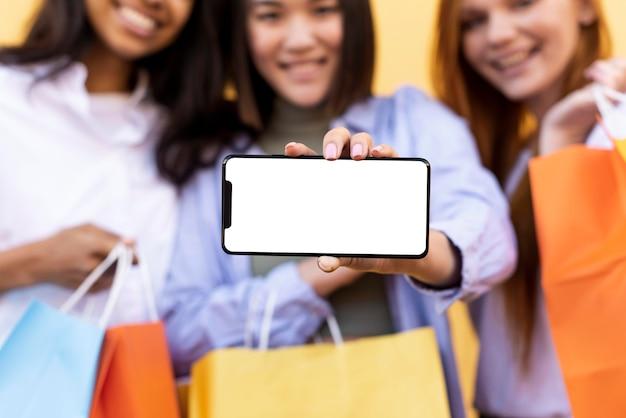 Mejores amigos con bolsas de la compra y un teléfono en blanco