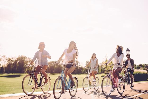 Mejores amigos y camino por delante. grupo de jóvenes en bicicleta a lo largo de una carretera y mirando feliz