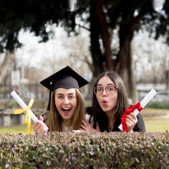 Mejores amigos en la ceremonia de graduación divirtiéndose