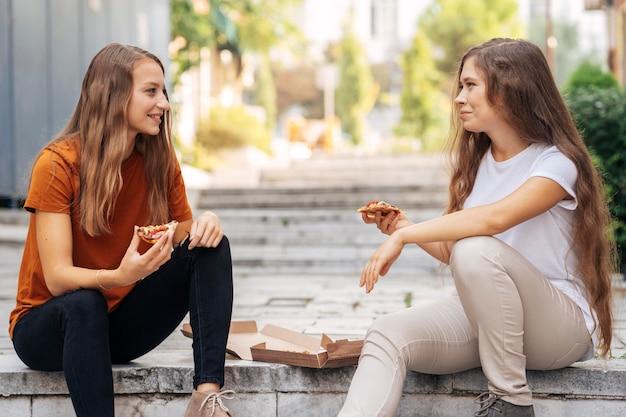 Mejores amigos comiendo una rebanada de pizza