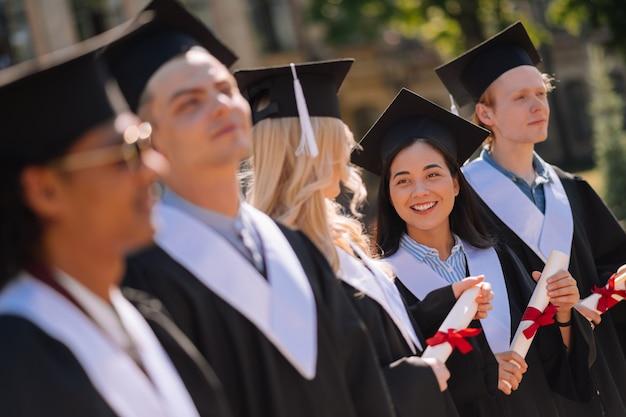 Mejores amigos. dos amigos sonrientes hablando sosteniendo sus nuevos diplomas durante la ceremonia de graduación.