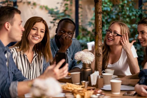 Los mejores amigos están charlando y riendo con sabrosos aperitivos en la terraza.