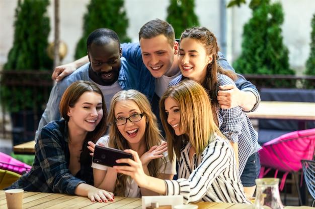 Los mejores amigos están tomando fotos autofotos en el teléfono inteligente en el acogedor restaurante