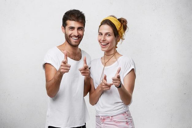 Mejores amigos masculinos y femeninos con expresión positiva mirando con agradables sonrisas apuntando con los dedos divirtiéndose y descansando posando