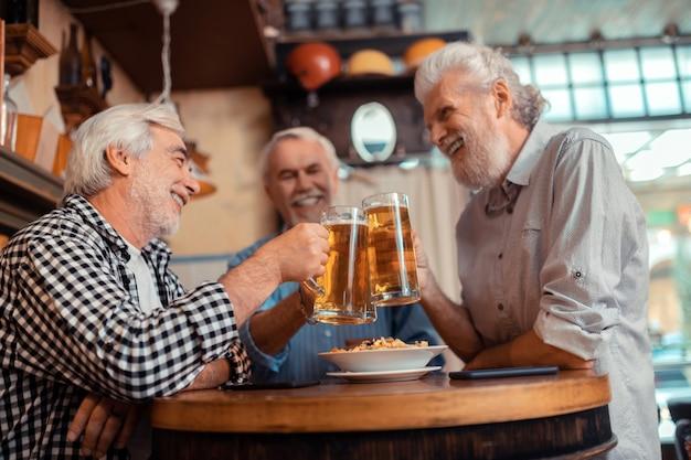 Mejores amigos. mejores amigos que se sienten alegres mientras beben cerveza juntos en el pub