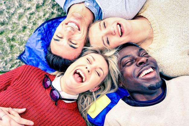 Mejores amigos multirraciales divirtiéndose y riendo juntos al aire libre en primavera - concepto de amistad feliz con jóvenes en ropa de moda - punto de vista al revés - aspecto filtrado vintage suave