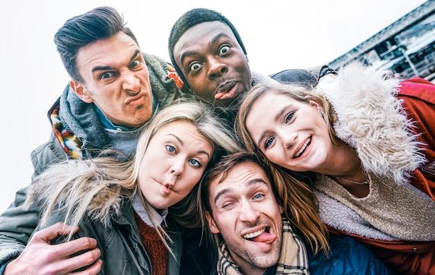 Mejores amigos multirraciales que toman selfie al aire libre en ropa de otoño invierno