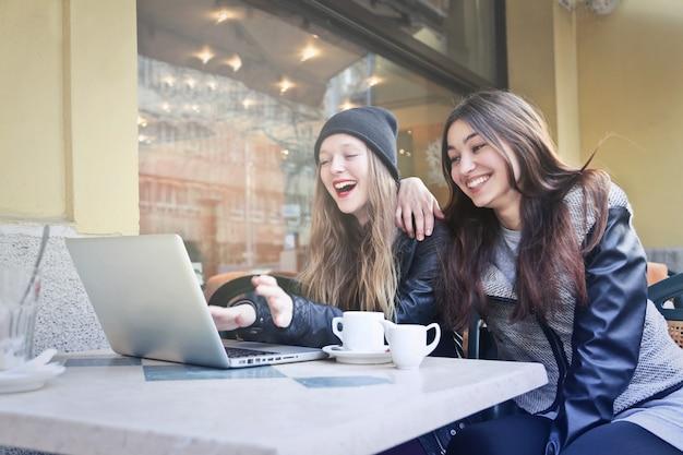 Mejores amigos navegando en internet en un café