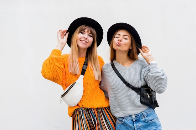 Mejores amigos, pareja de chicas elegantes posando en blanco