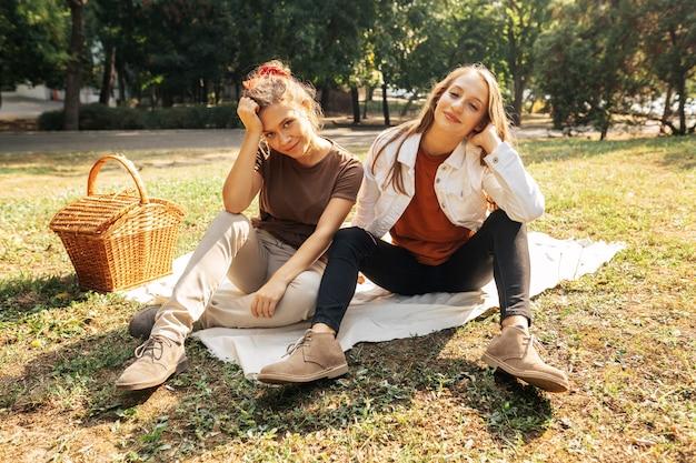Mejores amigos posando sobre una manta de picnic