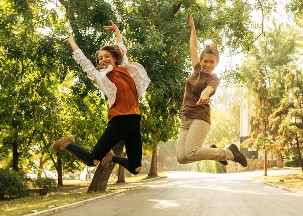 Mejores amigos saltando al aire libre