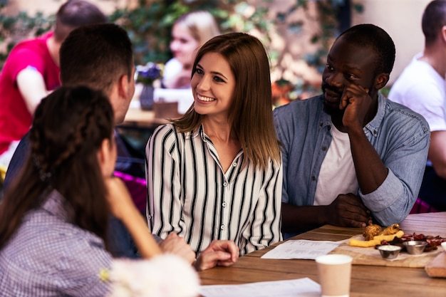 Mejores amigos sentados alrededor de la mesa en una terraza de un café tranquilo y acogedor