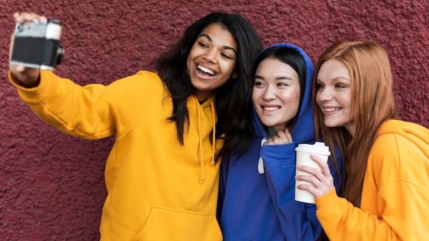 Mejores amigos en sudaderas con capucha tomando un selfie con una cámara