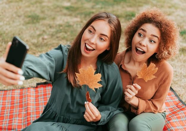 Mejores amigos tomando un selfie juntos en otoño