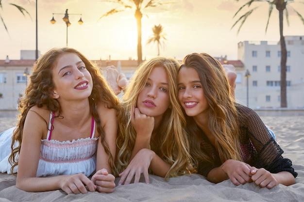 Las mejores chicas amigos en la arena de la playa puesta