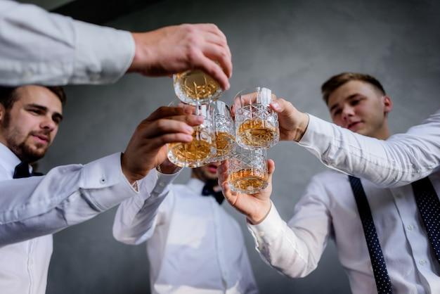 Los mejores hombres con vasos llenos de bebidas alcohólicas vestidos con atuendos formales
