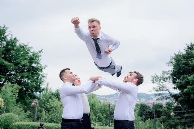 Los mejores hombres vestidos con atuendos formales arrojan al novio como un superhombre, al aire libre, trabajo en equipo