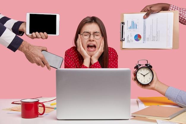 Melancolía, concepto de trabajo. mujer triste deprimida llora de desesperación, mantiene mouh abierto, usa anteojos redondos, tiene mucho trabajo, se prepara para el examen