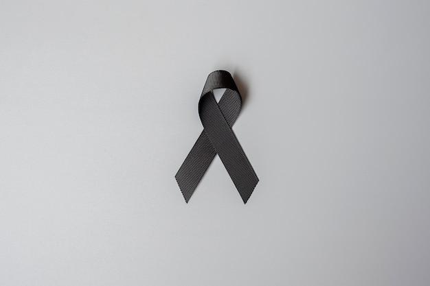 Melanoma y cáncer de piel, mes de concientización sobre lesiones por vacunas y conceptos de descanso en paz. cinta negra sobre fondo gris
