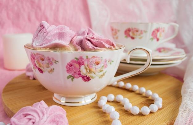 Melcochas rosadas en una taza con café. estilo en mal estado