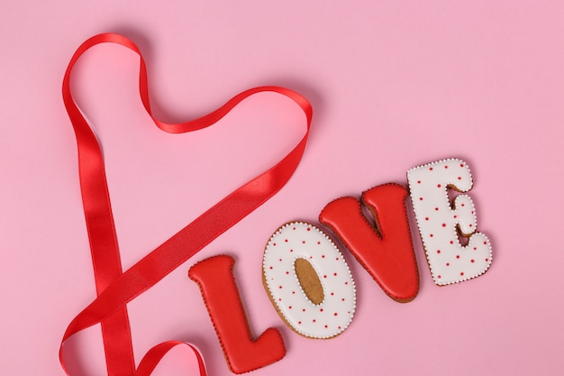 Melindres caseros con letras amor para el día de san valentín ubicado sobre un fondo rosa, vista superior