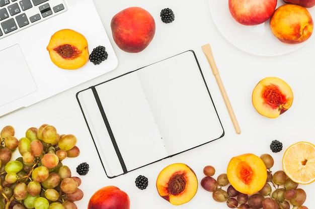 Melocotón a la mitad; uvas y moras en la computadora portátil; diario y pluma sobre fondo blanco