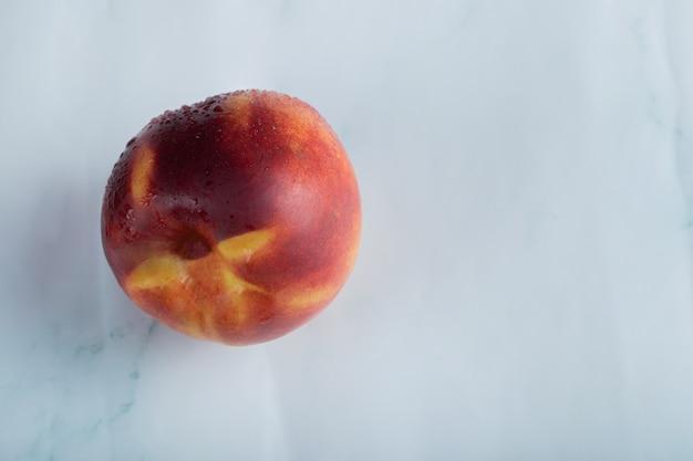 Un melocotón rojo sobre una superficie blanca con gotas de agua