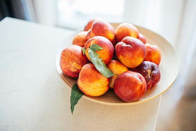 Melocotones maduros frescos con hojas en un plato de madera sobre una mesa de la cocina contra la ventana. concepto de alimentos orgánicos y prevención de la deficiencia de vitaminas. frutas para cocinar.
