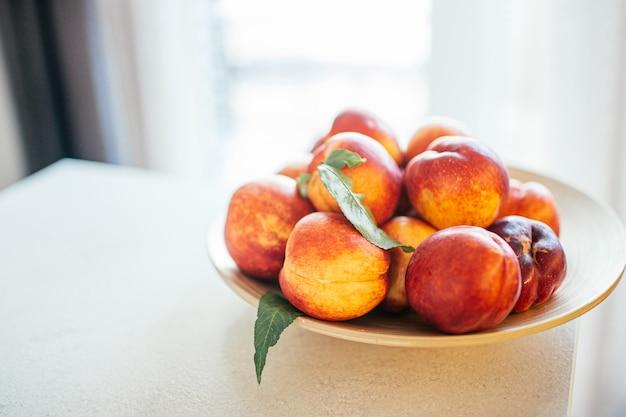 Melocotones maduros frescos con hojas en un plato de madera sobre una mesa de la cocina contra la ventana. concepto de alimentos orgánicos y prevención de la deficiencia de vitaminas.