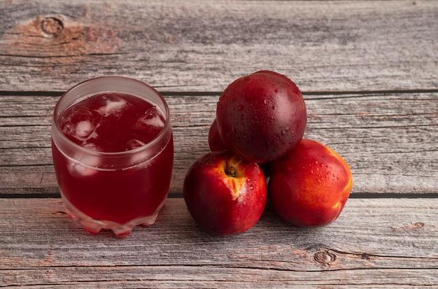 Melocotones rojos con una taza de bebida helada en una mesa de madera