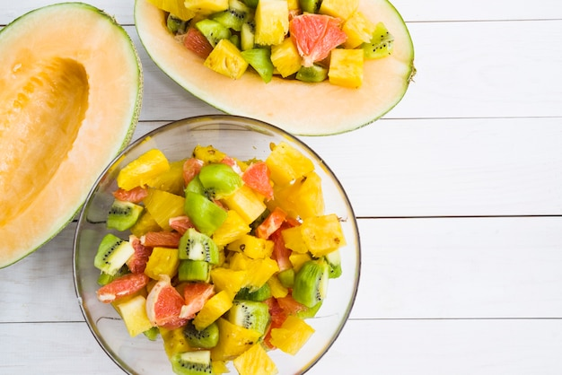 Melón a la mitad con rodajas de frutas en un tazón